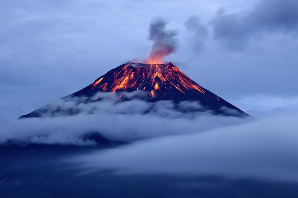 Eruption of tungurahua volcano at dusk with lava flows.
